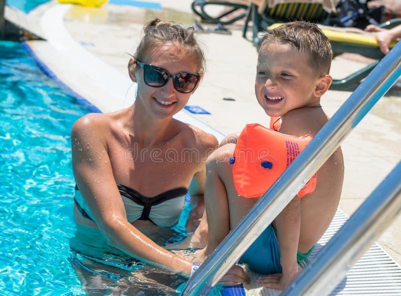 愉快的年轻母亲和她的小儿子,可爱的笑的男婴获得乐趣一起在一个室外游泳池在一个热的夏天 库存照片