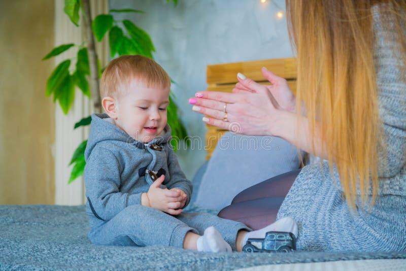 愉快的年轻母亲和她的演奏togerher的小儿子 免版税库存图片