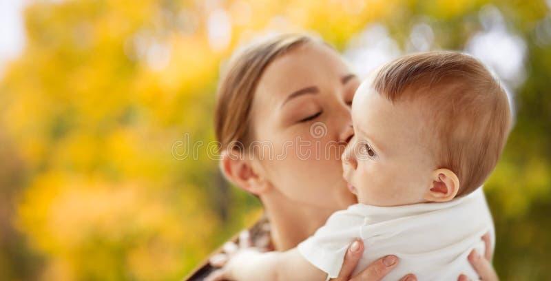 愉快的年轻母亲在秋天的亲吻一点婴孩 图库摄影
