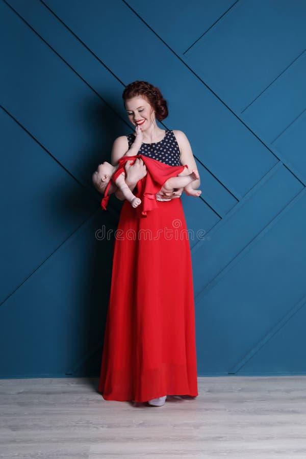 愉快的年轻母亲在蓝色演播室抱着红色的逗人喜爱的婴孩 免版税库存图片
