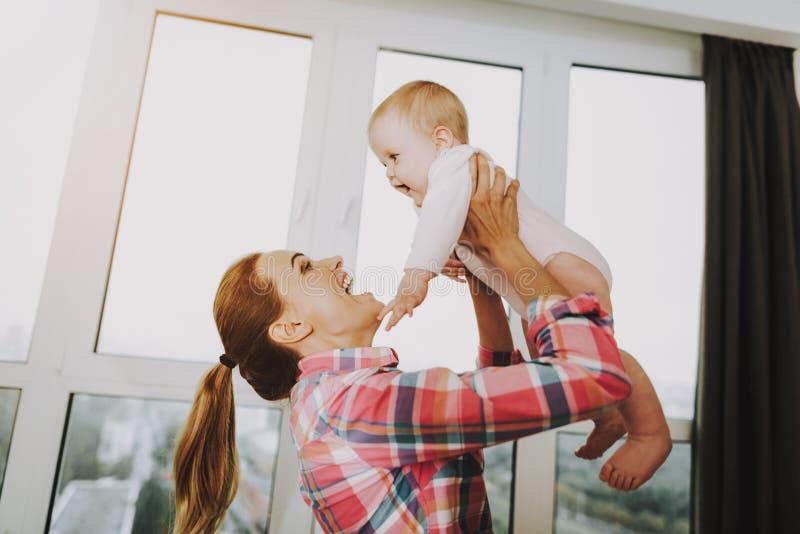 愉快的年轻母亲投掷逗人喜爱的孩子户内 免版税图库摄影