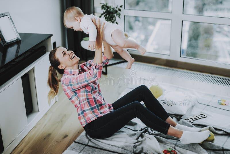 愉快的年轻母亲投掷逗人喜爱的孩子户内 免版税库存图片