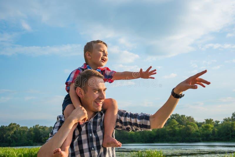 愉快的年轻父亲举行他的在他的肩膀的儿子肩扛乘驾 库存照片