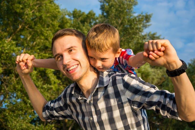 愉快的年轻父亲举行他的在他的肩膀的儿子肩扛乘驾 免版税库存图片
