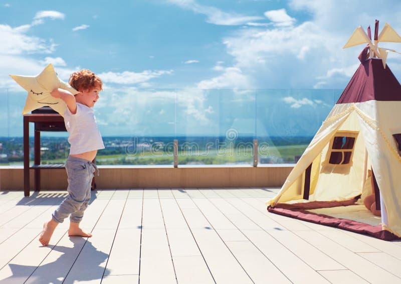 愉快的年轻男孩,使用在夏天露台的纺织品圆锥形小屋帐篷附近的孩子 免版税库存图片