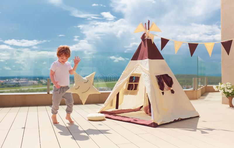 愉快的年轻男孩,使用在夏天露台的纺织品圆锥形小屋帐篷附近的孩子 库存照片