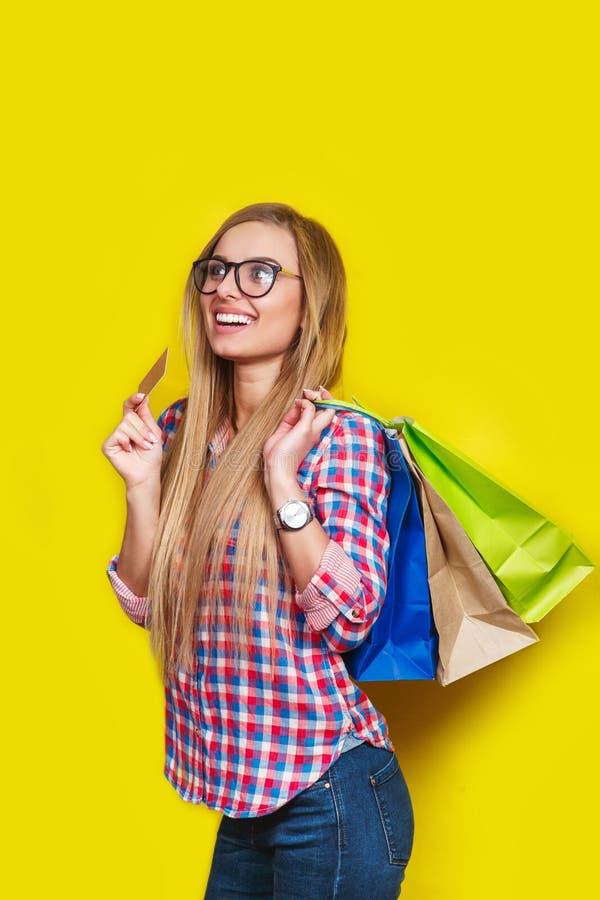 愉快的年轻白肤金发的妇女画象拿着信用卡和五颜六色的购物袋的玻璃的,隔绝在黄色背景 图库摄影