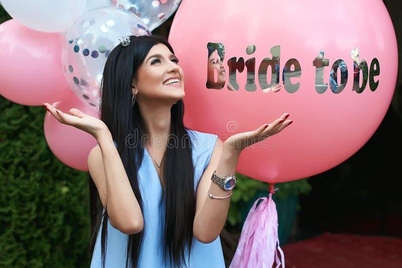 愉快的年轻美丽的深色的新娘是与黑发和银加冠微笑和延长她的在喜悦的手  免版税图库摄影