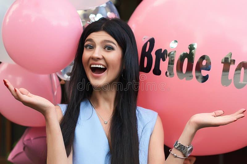 愉快的年轻美丽的深色的新娘是与黑发和银加冠微笑和延长她的在喜悦的手  库存照片