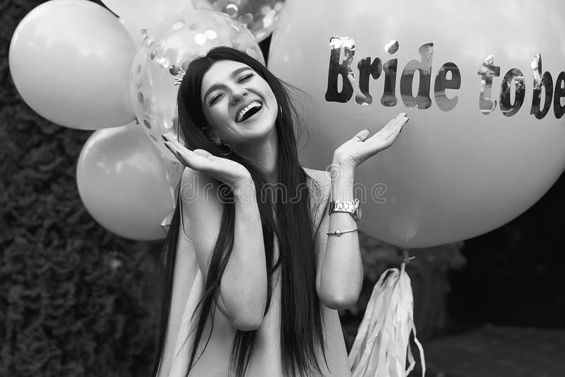 愉快的年轻美丽的深色的新娘是与黑发和银加冠微笑和延长她的在喜悦的手  图库摄影