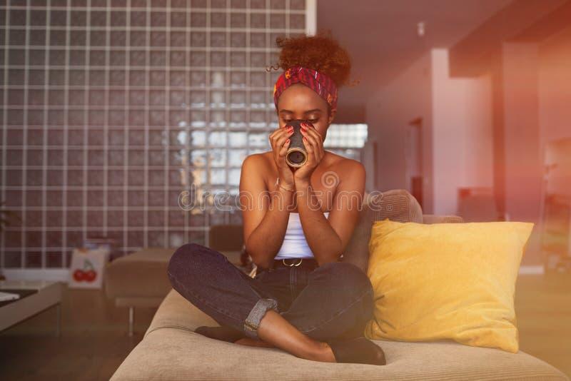 愉快的年轻美国非洲妇女用在沙发的长的卷发放松的和饮用的咖啡在现代家 免版税库存图片
