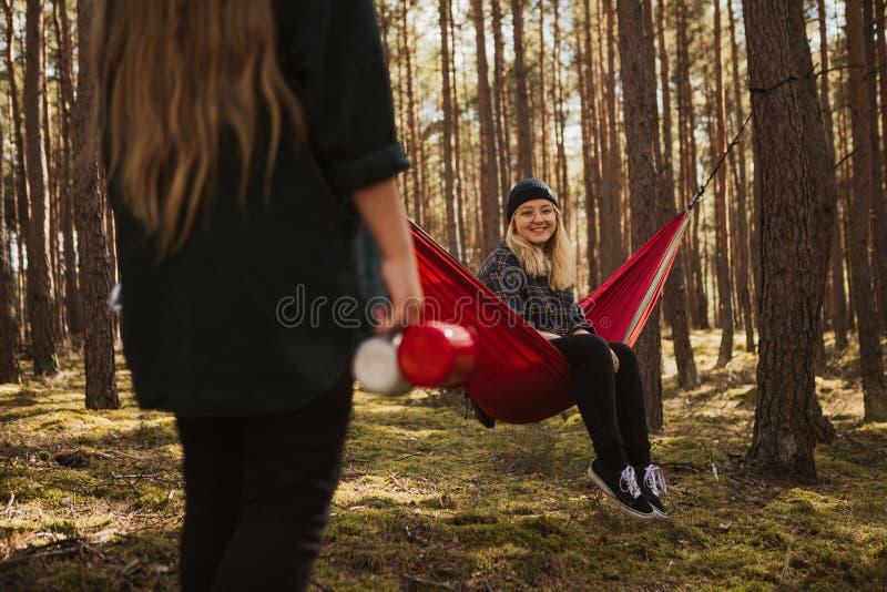 愉快的年轻行家女孩在夏天森林里享受生活和自然在吊床有其他妇女的 免版税库存图片