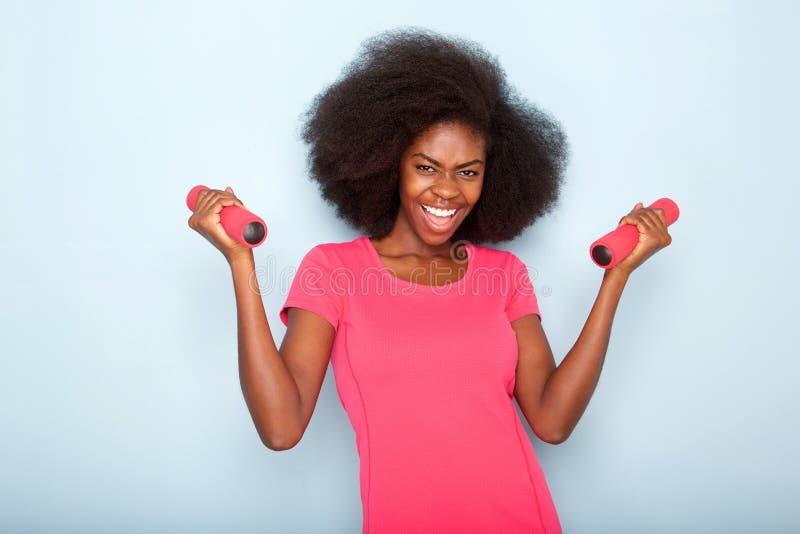 愉快的年轻黑人妇女藏品锻炼重量的关闭 库存图片