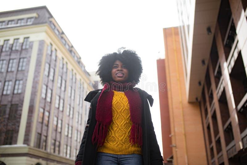 愉快的年轻黑人妇女走到城市街道 免版税库存照片