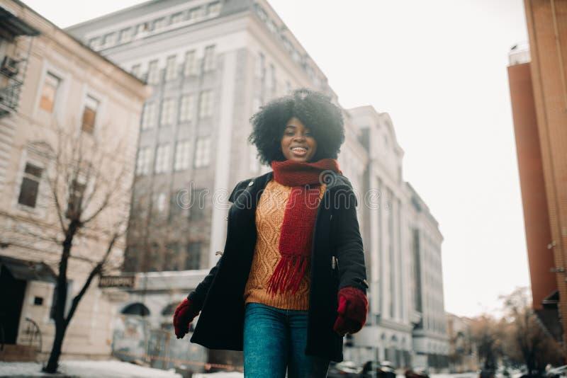 愉快的年轻黑人妇女走到城市街道 免版税库存图片