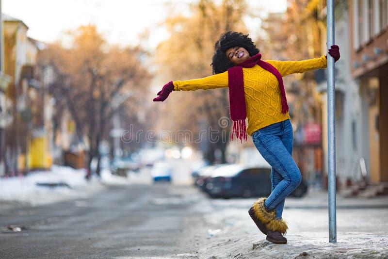 愉快的年轻黑人妇女走到城市街道 库存照片