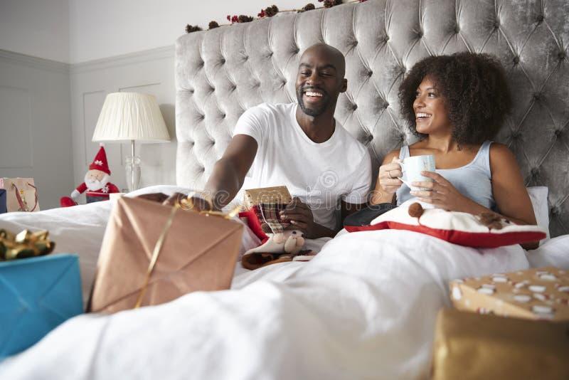 愉快的年轻黑夫妇在互相给礼物的床上坐圣诞节早晨,低角度 免版税库存照片