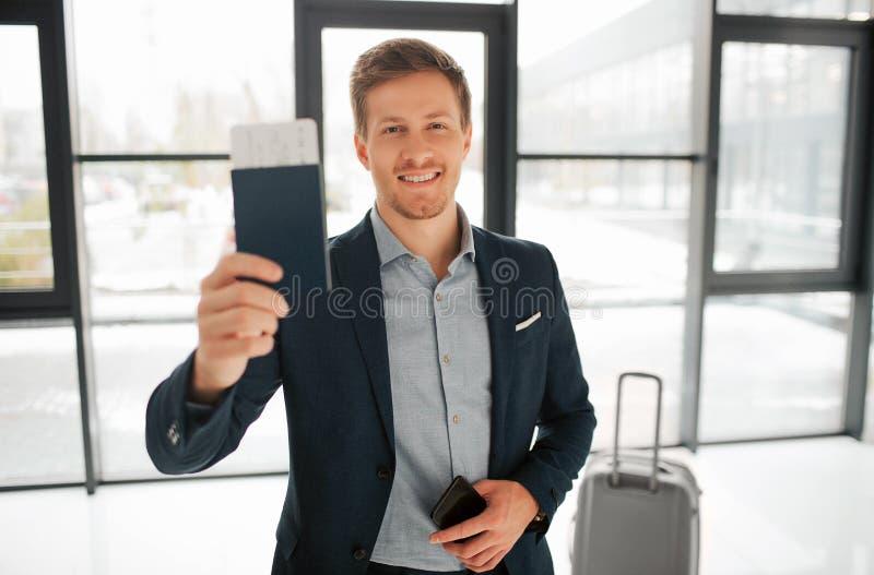 愉快的年轻buisnessman立场在机场大厅里和与票的展示护照 他在照相机和微笑看 人有电话 免版税库存图片