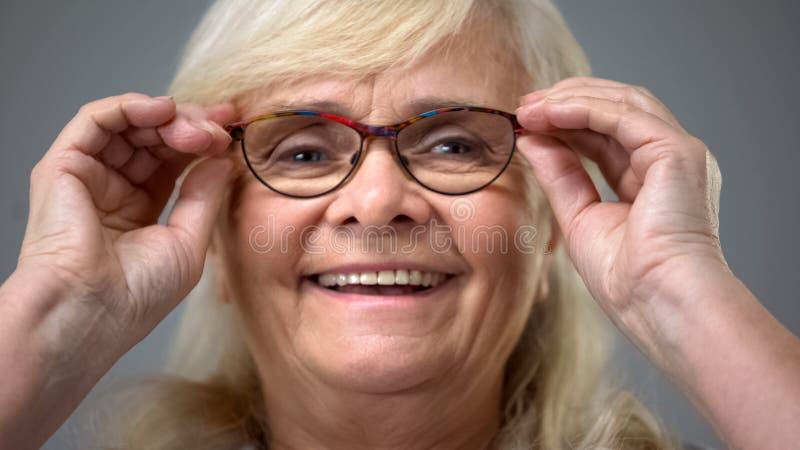 愉快的年迈的夫人投入在新的玻璃的,参观的眼科学诊所,眼力 免版税库存照片