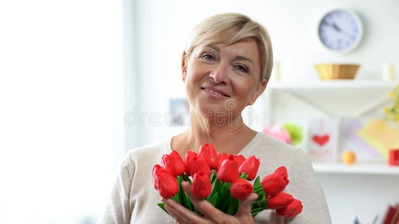 愉快的年迈的女性举行的花束从钦佩者的郁金香和微笑对照相机 库存照片