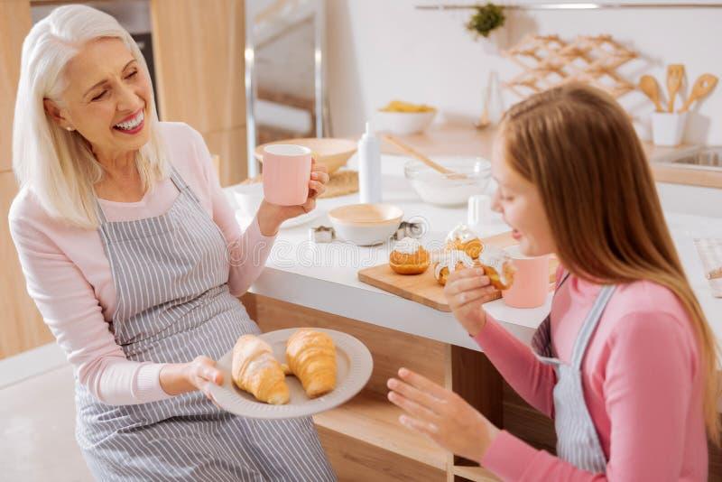愉快的年迈的妇女提供的新月形面包 免版税库存图片