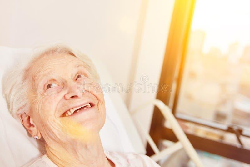 愉快的年长妇女在床上在老人院 免版税库存照片
