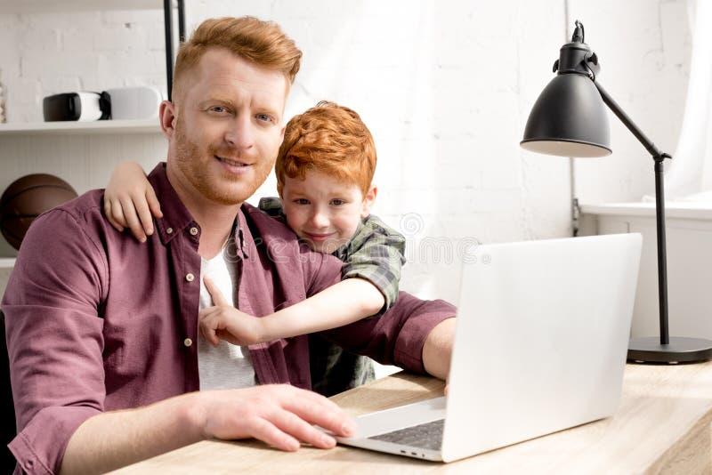 愉快的微笑对照相机的父亲和儿子,当使用膝上型计算机一起时 免版税库存图片