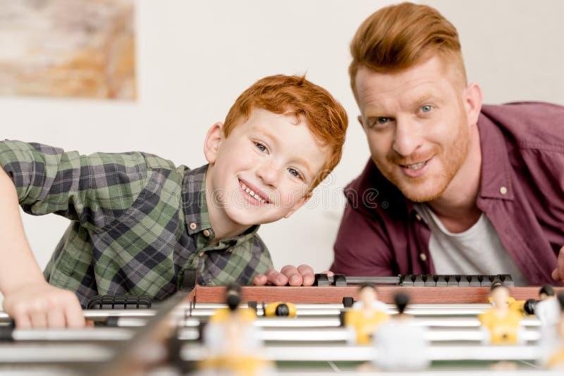 愉快的微笑对照相机的红头发人父亲和儿子,当一起踢桌橄榄球在家时 免版税图库摄影