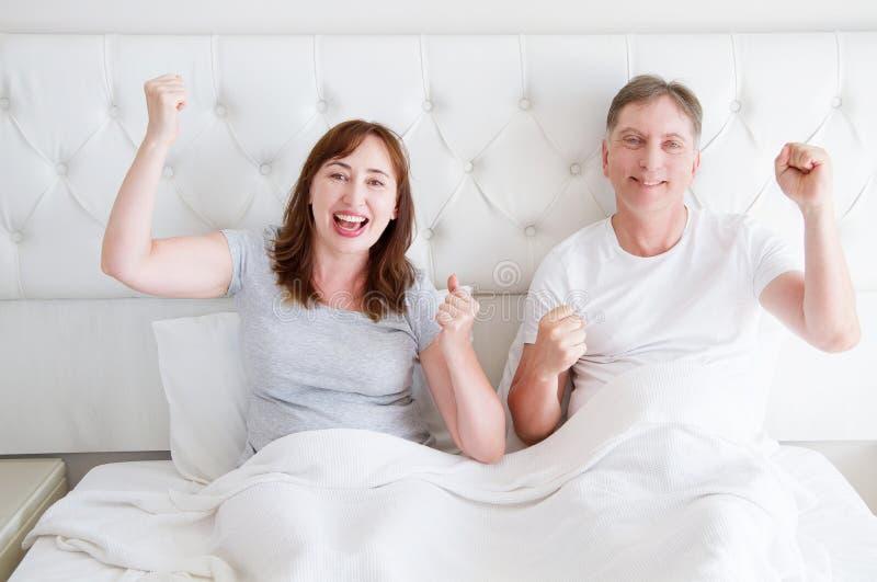 愉快的微笑的中年夫妇在 T恤杉的床上 健康家族关系 复制空间 库存图片