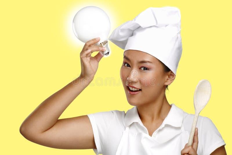 愉快的微笑的亚裔中国妇女厨师在工作 免版税图库摄影