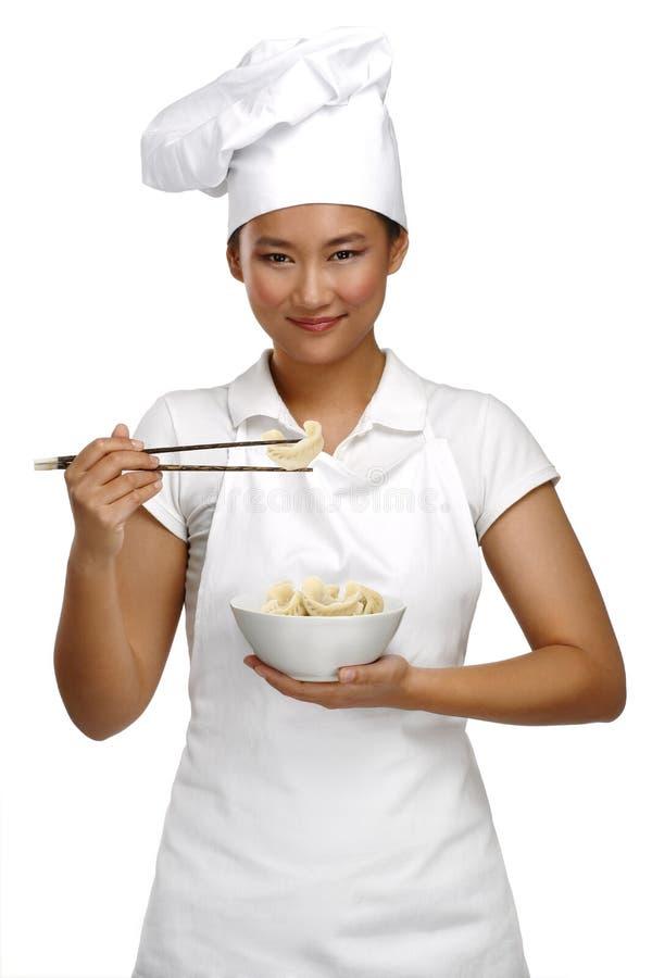 愉快的微笑的亚裔中国妇女厨师在工作 图库摄影