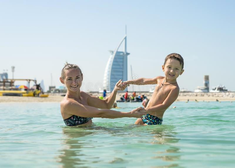 愉快的微笑的使用和跑在海滩的母亲和她的儿子 友好的家庭的概念 免版税库存图片