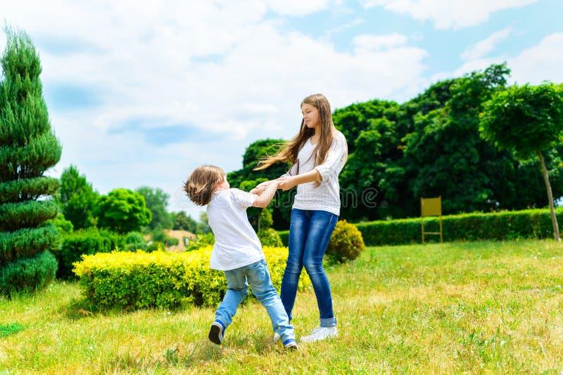 愉快的微笑的使用在草的女孩和男孩 免版税库存图片