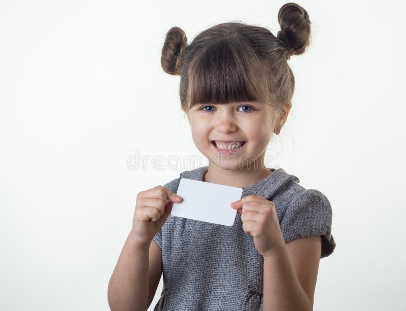 愉快的微笑的儿童藏品折扣白色卡片在她的手上 与信用卡的孩子 库存图片