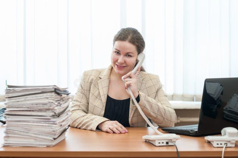 愉快的微笑的办公室助理坐在书桌和叫用电话 免版税库存照片