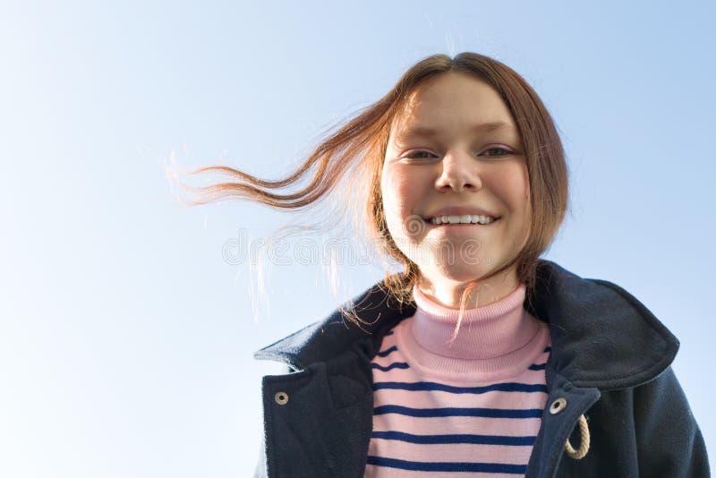 愉快的微笑的十几岁的女孩画象外套的 库存照片
