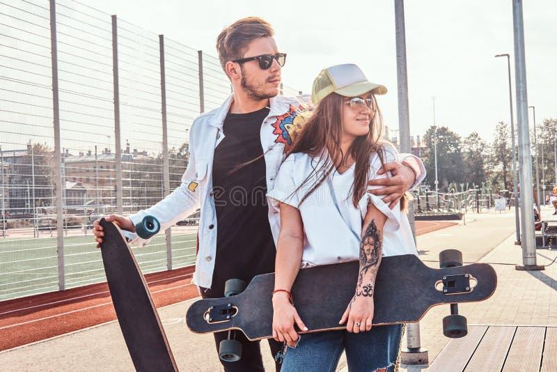 愉快的微笑的夫妇在有他们的longboards的夏天街道上站立 库存照片