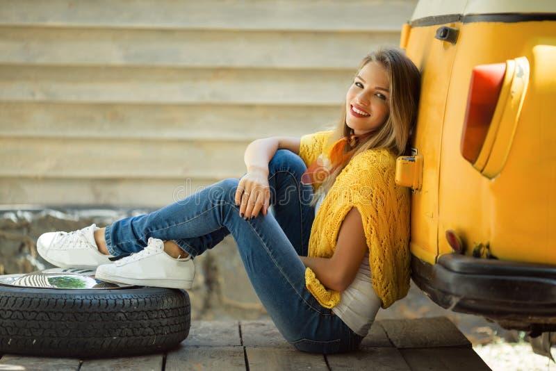 愉快的微笑的女孩在有轮胎的,秋天概念老减速火箭的公共汽车附近穿黄色毛线衣 库存照片