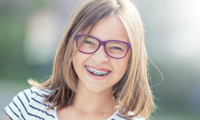愉快的微笑的女孩画象戴牙齿括号和眼镜的 库存照片