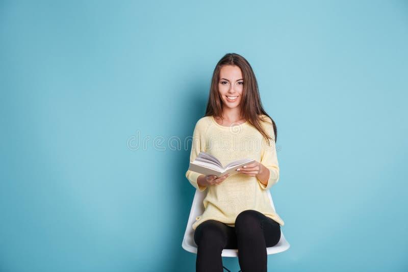 愉快的微笑的女孩阅读书和开会在椅子 库存照片