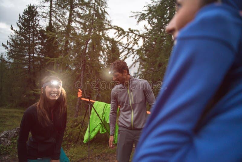 愉快的微笑的妇女和人有前灯手电的在野营附近期间 小组朋友人夏天 库存图片