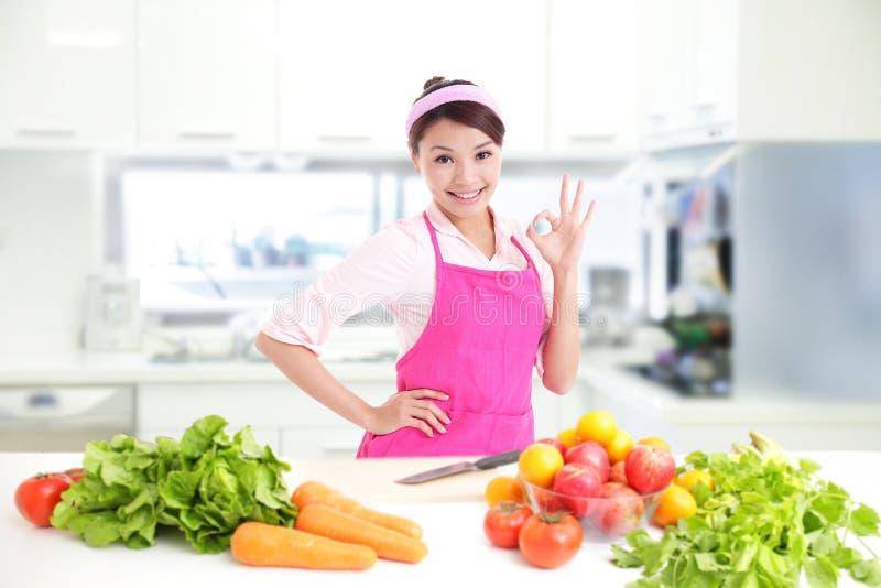 愉快的微笑的妇女在厨房里 库存照片