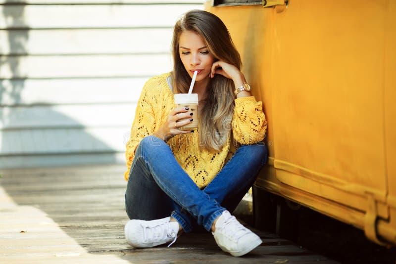 愉快的微笑的妇女在老减速火箭的公共汽车附近佩带黄色毛线衣饮用的咖啡拿铁 免版税库存图片