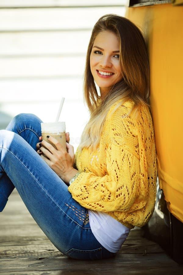 愉快的微笑的妇女在老减速火箭的公共汽车附近佩带黄色毛线衣饮用的咖啡拿铁 库存照片