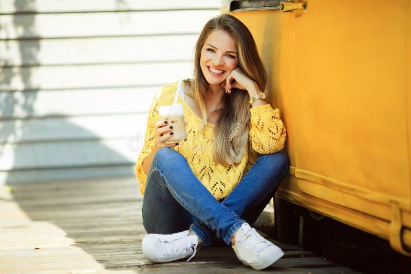 愉快的微笑的妇女在老减速火箭的公共汽车附近佩带黄色毛线衣饮用的咖啡 库存图片