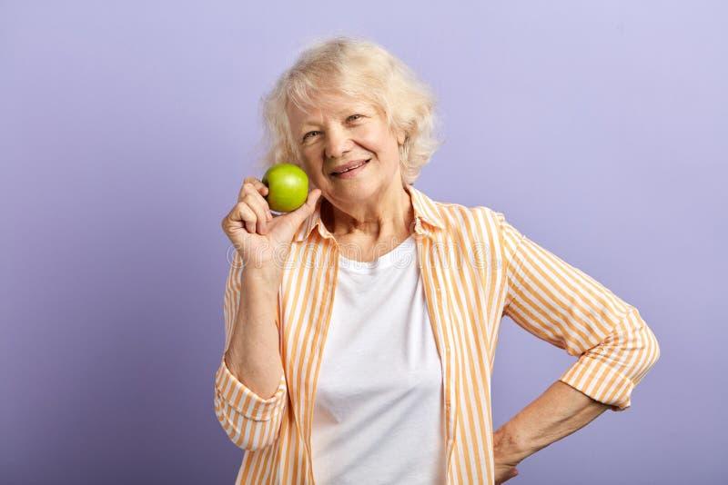 愉快的微笑的妇女她的拿着绿色苹果和微笑对照相机的60 图库摄影