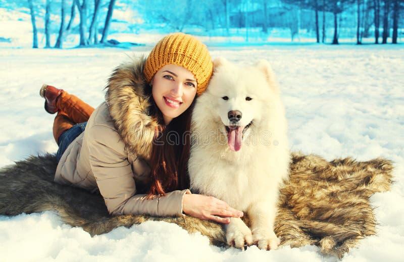 愉快的微笑的妇女所有者和白色萨莫耶特人在冬天尾随说谎在雪 免版税库存照片