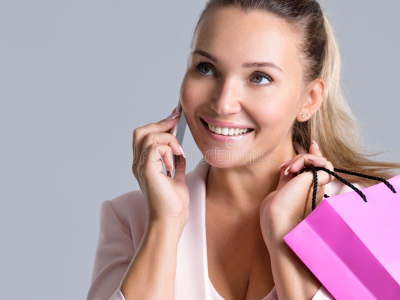 愉快的微笑的妇女画象有发表演讲关于上午的桃红色袋子的 免版税库存图片