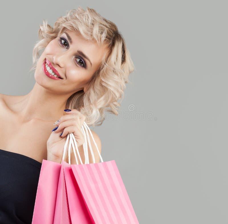 愉快的微笑的妇女画象 与桃红色购物带来的逗人喜爱的模型 免版税库存照片