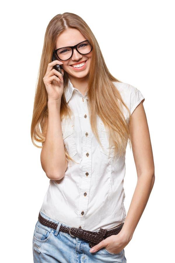愉快的微笑的妇女谈话在白色的手机 免版税库存照片